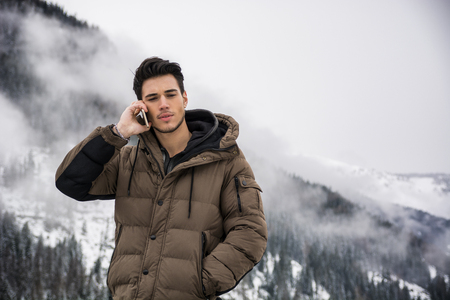 outerwear: Dark haired handsome young man in winter outerwear using cell phone or smartphone, outdoor at mountain with snowy landscape behind Stock Photo