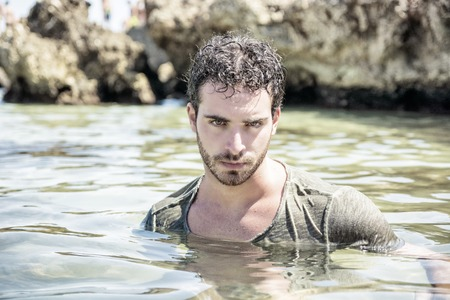 wet t shirt: Attractive young athletic man in the sea or ocean by the rocky shore, wearing wet t-shirt, serious expression Stock Photo