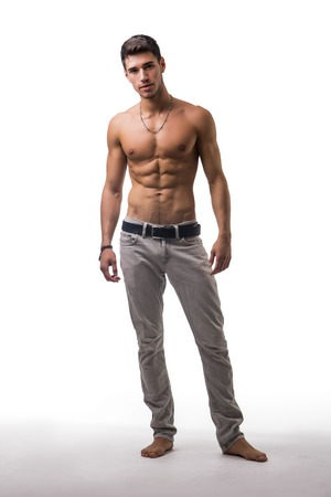 Full figure shot of handsome shirtless athletic young man in jeans, looking at camera in studio shot, isolated on white background