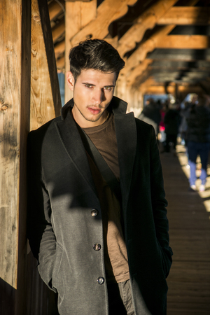 dark haired: Young dark haired man standing on wooden medieval footbridge in Switzerland while looking away