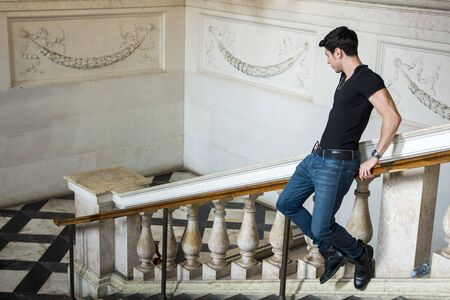 dark haired: Side view of young dark haired man going down on railing in museum. White walls decorated with ornament. Stock Photo