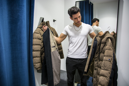 changing room: Young Handsome Man Trying on Clothes in Clothing Stores Changing Room in Front of a Mirror or in Room Closet