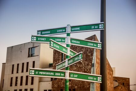 kilometre: Different geographical locations on crossroad signs against of buildings Stock Photo