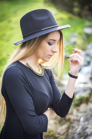 fedora: Pretty blonde young woman outdoor in city park, wearing short black dress and fedora hat Stock Photo