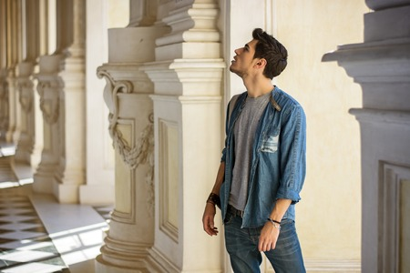 Half Body Shot of a Thoughtful Handsome Young Man, Looking Away Inside a Museum
