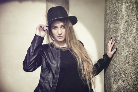 fedora: Portrait of attractive blonde young woman in black fedora hat and leather jacket looking at camera