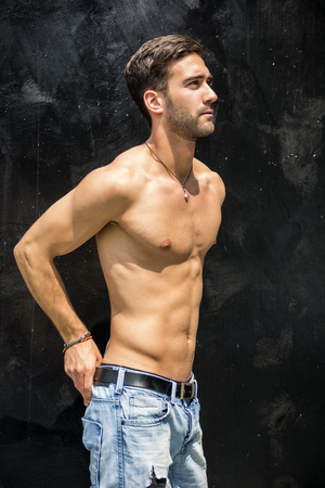 young unshaven: Handsome unshaven shirtless young man standing against black wall, looking to a side