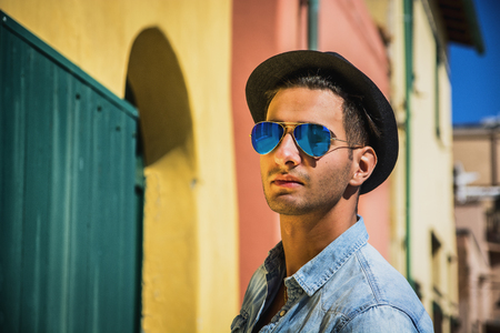 mirrored: Portrait of dark haired young man in blue mirrored sunglasses and black hat. Cityscape on background, with colorful houses in Italy