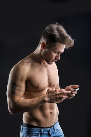 Handsome shirtless muscular young man using cell phone on dark background
