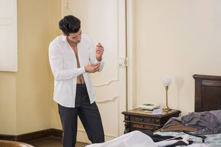 brunets: Handsome young man putting on white shirt while buttoning up sleeve in bedroom