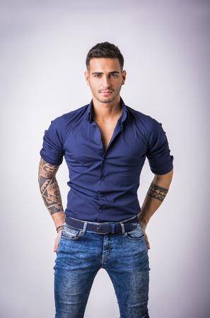 スタジオで白い背景に分離された青いシャツとジーンズのポーズでハンサムな若い男 写真素材