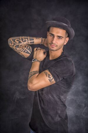 bowler hat: Handsome and stylish young man with black bowler hat and t-shirt. Cool tattoos on arms Stock Photo