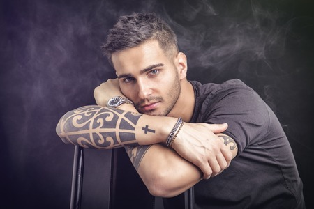 Handsome and stylish young man with black t-shirt. Cool tattoos on arms