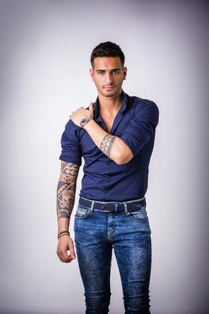 Beau jeune homme en chemise bleue et un jean posant sur fond gris en studio