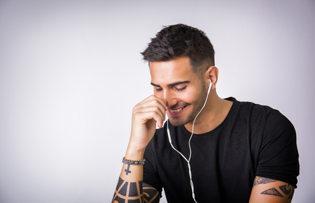 earphone: Attractive young man with earphones listening to music, on light background