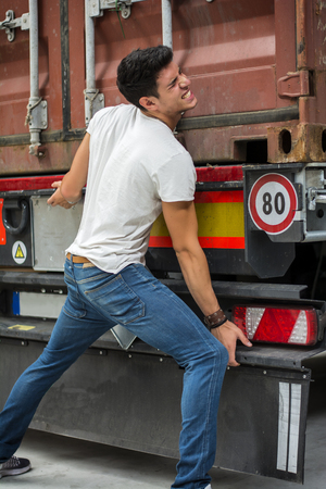 brunets: Young man squinting eyes in effort to lift heavy truck