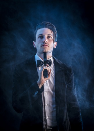 gun shot: Portrait of young handsome man in elegant smoking commiting suicide with gun on neck Stock Photo