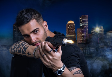 gunsight: Portrait of handsome young tattooed man shots with gun against someone at night in city Stock Photo