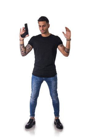 detained: Portrait of detained tattooed man with gun. Studio shot. Isolated on white background. Full length body shot