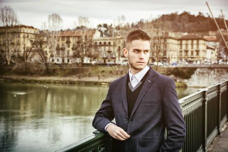 contemplative: Three-quarter length of contemplative light brown haired young man wearing grey jacket and denim jeans standing beside picturesque river in Turin, Italy