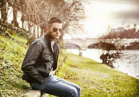 contemplative: Three-quarter length of contemplative light brown haired young man wearing grey jacket and denim jeans sitting on wall beside picturesque river in Turin, Italy