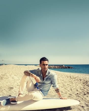 Élégant beau jeune homme dans des lunettes de soleil miroir assis sur planche de surf sur la plage en plein soleil