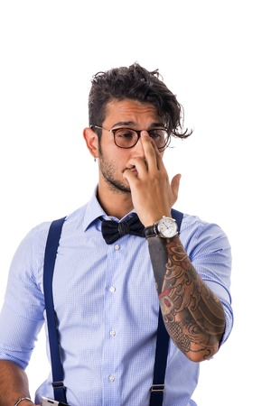 embarassed: Portrait of shy or embarassed young man in glasses,bow-tie,suspenders and shirt looking away. Studio shot Stock Photo