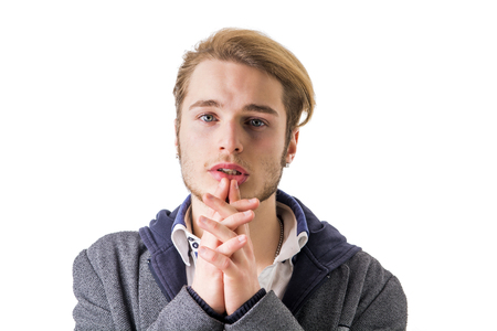 pleading: Needy, desperate young man pleading with hands joined as if praying to camera, isolated Stock Photo