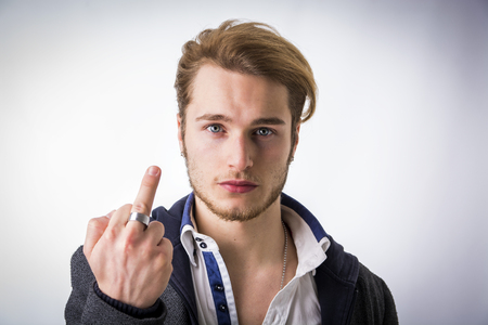 stern: Portrait of handsome blond young man, doing screw you sign, showing middle finger. Stern, severe expression