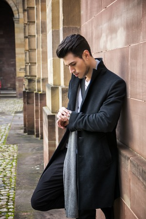 watch city: Handsome young man outdoor in winter fashion, checking the time on wrisst watch, wearing black coat and woolen scarf against historic wall in European city