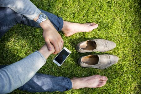 barefoot man: Unrecognizable barefoot man with shoes and cell on grass in sunlight.From above Stock Photo