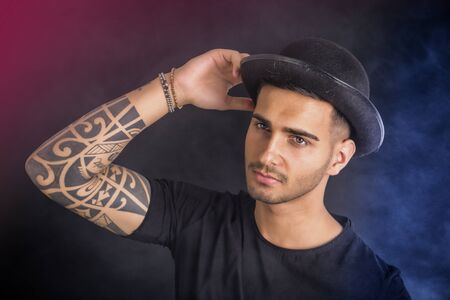 bowler: Handsome and stylish young man with black bowler hat and t-shirt. Cool tattoos on arms Stock Photo