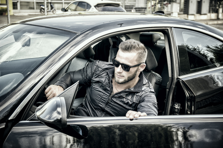 getting out: Portrait of young bearded man in sunglasses getting out of his new stylish polished car outdoor