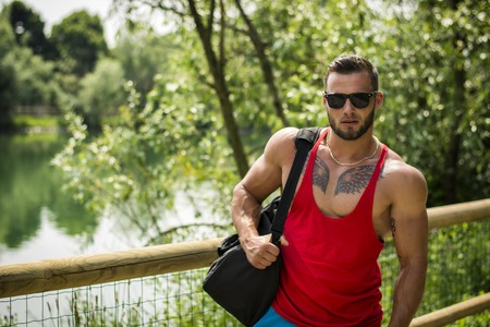 tanktop: Handsome Muscular Hunk Man Outdoor in City Park, During Daytime, Wearing Tanktop and Sunglasses Stock Photo