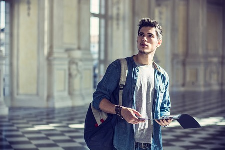 half body: Half Body Shot of a Thoughtful Handsome Young Man, Holding a Guide, Looking Away Inside a Museum Stock Photo