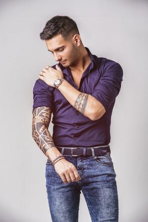 Beau jeune homme en chemise bleue et un jean posant sur fond blanc en studio