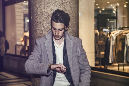 watch city: Elegant attractive young man outdoor wearing wool coat, in European city, looking at wrist watch