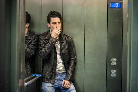 Scared young man desperate in stuck elevator screaming, looking very upset