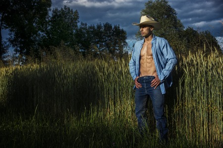hay field: Portrait of sexy farmer or cowboy in hat looking to a side, while standing next to hay field in countryside Stock Photo