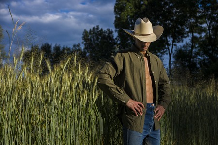 Portrait of sexy farmer or cowboy in hat looking to a side, while standing next to hay field in countryside Stockfoto