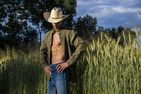 man in field: Portrait of sexy farmer or cowboy in hat looking to a side, while standing next to hay field in countryside Stock Photo