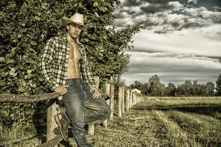 Portrait of sexy farmer or cowboy in hat looking at camera while leaning on wooden fence in countryside Stock Photo