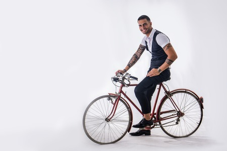 Portrait of young tattooed man in elegant clothes and shoes riding a bicycle.Isolate.Studio shot.