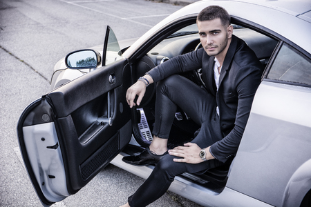 Portrait of young attractiave man in business suit sitting in his new stylish polished car outdoor