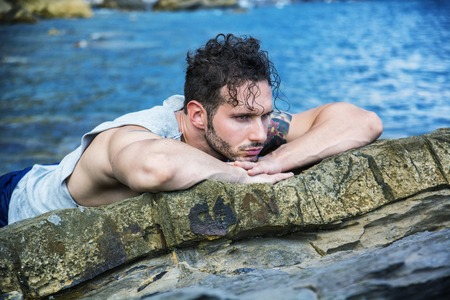 tanktop: Handsome muscular man on the beach lying on rocks, looking at camera