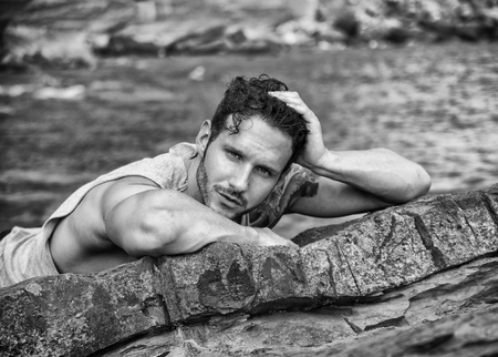 beach hunk: Handsome muscular man on the beach lying on rocks, looking at camera