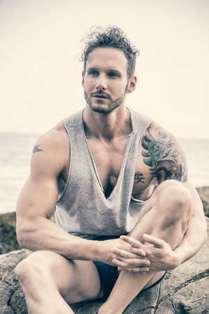 beach hunk: Handsome muscular man on the beach sitting on rocks, looking at camera Stock Photo