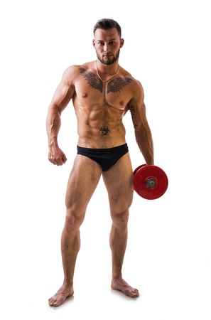 Muscular sexy shirtless young man exercising biceps with dumbbell, isolated on white. Full length shot