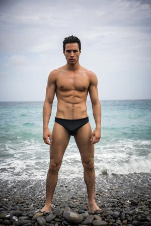 Aantrekkelijke gespierde jonge shirtless atletische man die zich naast het water door de zee of oceaan kust, het dragen van stammen of zwemmen pak, kijken naar de camera in een bewolkte zomerdag