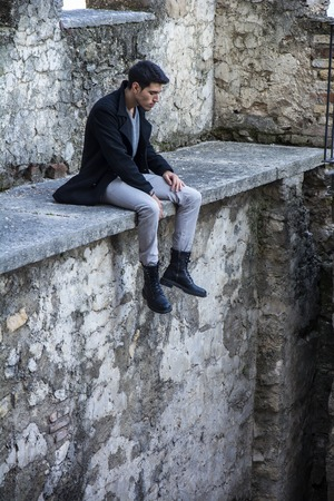 goodlooking: Portrait of good-looking man looking down while sitting on stone edge Stock Photo